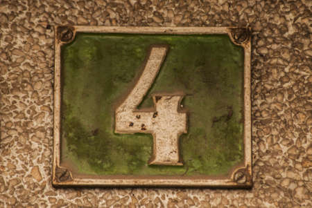 Old retro weathered cast iron plate with number 4 closeup