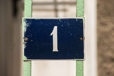 Weathered grunge square metal enamelled plate of number of street address with number 1