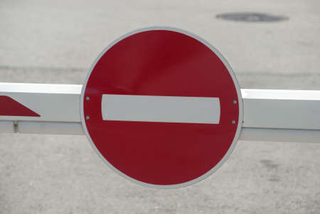 Red road traffic stop sign closeup on car parking barrier