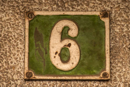 Old retro weathered cast iron plate with number 6 closeup
