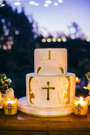 Christening cake in hall with candles on wooden board