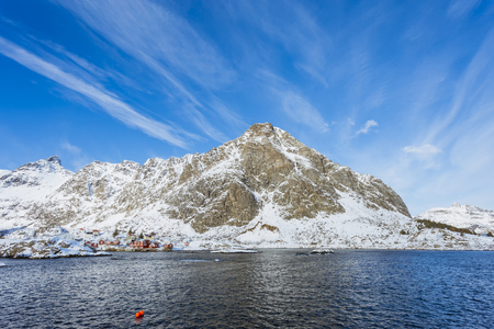 Beautiful Norwegian winter landscape with a sea bay and high mountains with small fishing houses on the shore, sunny day in the Lofoten Islands Stok Fotoğraf - 123547228
