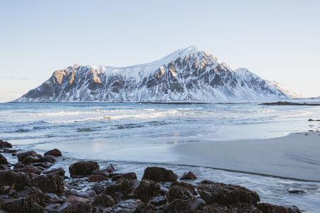 A magnificent panorama of the ocean coast, the waves wash the sandy coast, big rocks, a winter landscape with mountains in Norway on the Lofoten Islands