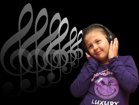 Little girl is listening music with headphone Stock Photo