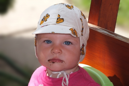 Baby is messed with chocolate on her face Stock Photo