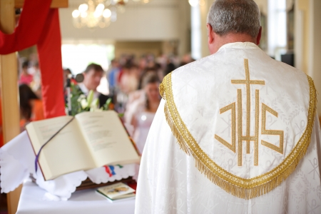 Bride and groom during a wedding ceremony in the background and the priest i the foreground