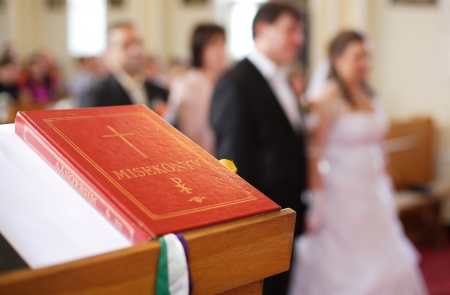 Young couple in a church with a book in a foreground photo