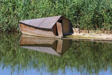 Old ark in a pond is mirroring in the water photo