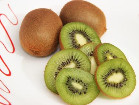 Whole kiwi fruit and its sliced segments isolated on white background