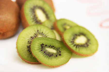 Whole kiwi fruit and it's sliced segments isolated on white background photo