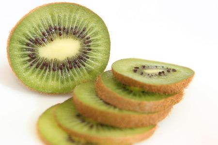 Whole kiwi fruit and it's sliced segments isolated on white background
