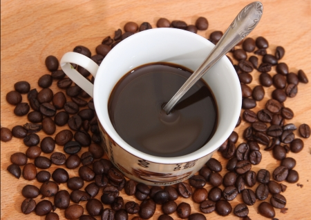 Cup of coffee on a wooden table with roasted coffee beans  Stock Photo