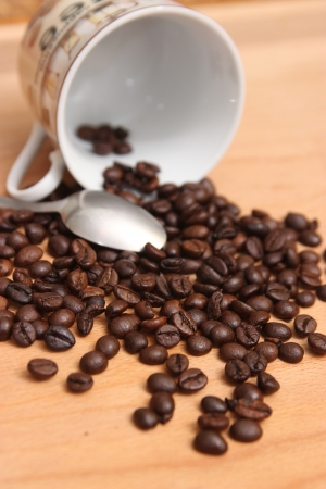 Cup of coffee on a wooden table with roasted coffee beans  photo