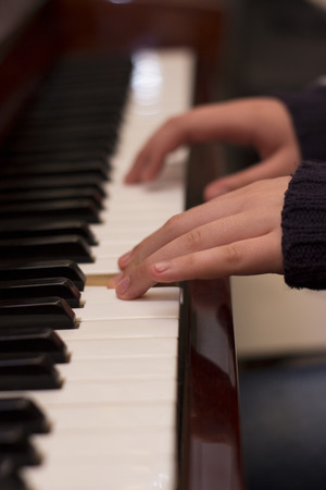 warble: Childs fingers are playing music on a piano