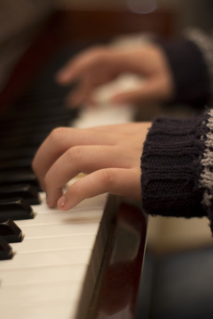 grand kids: Childs fingers are playing music on a piano