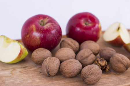 Apple and walnuts on a wooden table