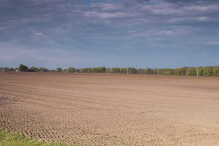 Plowed field with cloudy sky - outdoor photography Stock Photo