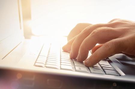 dirección empresarial: Las manos del hombre s escribiendo en el teclado de la computadora portátil