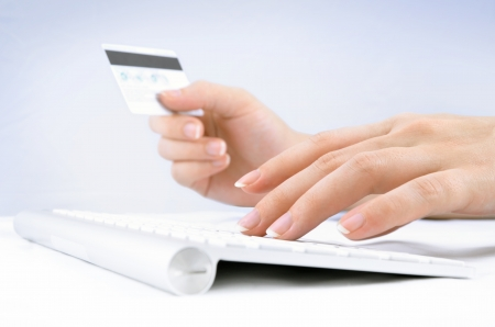 entering information: Woman hands holding a credit card and using computer keyboard for online shopping