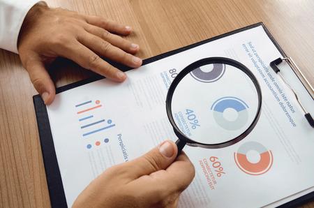 Investigación de mercado. El hombre de negocios mano que sostiene la lupa y más cerca informe del estudio de investigación de mercado. Concepto para la bandera página web, fondo, plantilla de presentación y materiales de marketing.