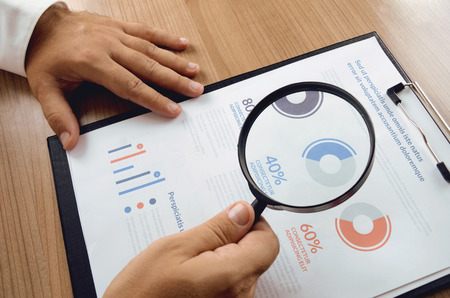 Market research. Businessman hand holding magnifier and closer study report from market research. Concept for website banner, background, presentation template and marketing materials. Archivio Fotografico