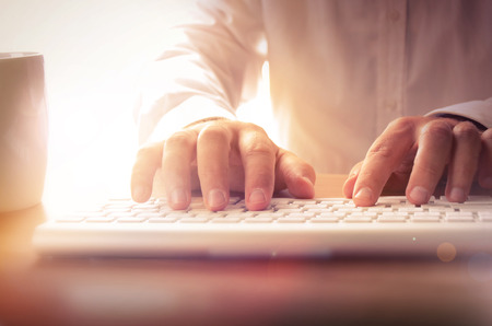 mecanografía: Primer plano de manos escribiendo en el teclado del hombre. La imagen se puede utilizar para el fondo, bandera del Web site, materiales promocionales, carteles, plantillas de presentación, publicidad y materiales impresos.