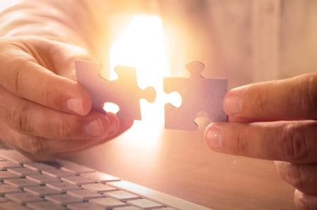 Nahaufnahme des Mannes Hände halten Puzzleteile. Bild für den Hintergrund, Web-Banner, Werbematerial, Poster, Präsentationsvorlagen, Werbe- und Druckmaterialien verwendet werden.