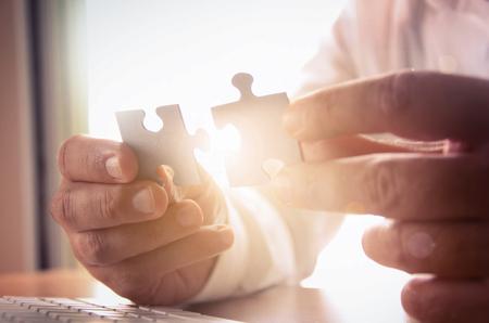 sol radiante: Soluciones de negocio, el éxito y la estrategia concepto. Mano de empresario conectar rompecabezas. Foto de archivo