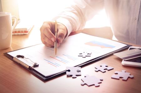 ビジネスマンは、パズルのピース、スマート フォン、クレジット カード、コーヒー カップの木製オフィス デスクで金融レポートで作業します。ビ 写真素材