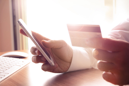 online payment: Closeup of mans hands holding credit cards and using mobile phone. Concept for m-commerce, online shopping, m-banking, internet security. Stock Photo