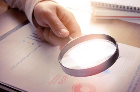 lupa: Análisis de negocios y estadísticas. Empresario informe del estudio utilizando una lupa.
