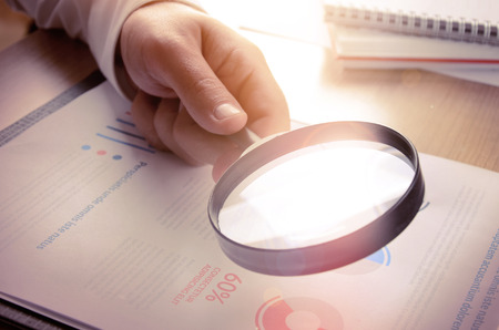 businessman: Business analytics and statistics. Businessman study report using a magnifying glass.