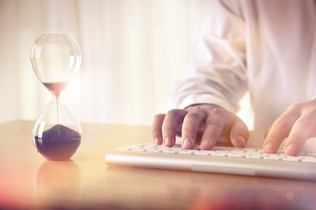 Time management concept. Mans hands typing on computer keyboard next to a hourglass. Concept for background, website banner, promotional materials, presentation templates, advertising.