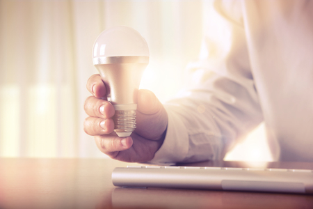 Big idea. Mans hand holding a light bulb above the keyboard. Concept for business idea and solutions, brainstorming, startup, innovation,  creative work, consulting, research and development. Stock Photo