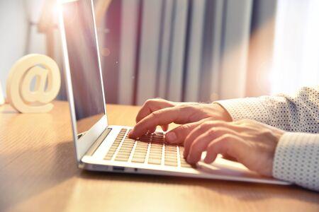 Internet service. Man's hands typing on laptop keyboard.