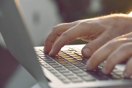 Close up of man's hands typing on laptop keyboard. Foto de archivo
