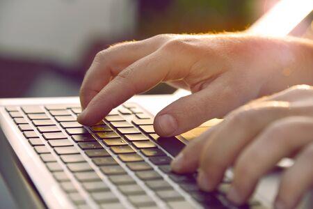 Man's hands typing on laptop keyboard.