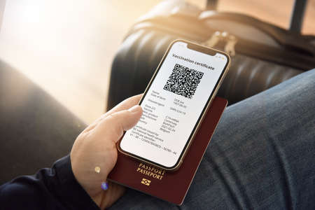 Digital certificate of vaccination against. A man holds a passport and a mobile phone next to a travel bag. Travel concept during pandemic. Imagens