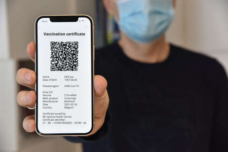 Man with face mask holding mobile phone with digital green certificate of vaccination against , a negative PCR test or recovery from . Travel concept during pandemic.