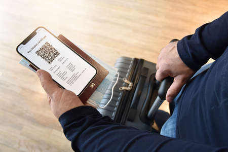 Travel and tourism concept during pandemic. Man holds smartphone with digital certificate of vaccination against  passport, face mask in one hand, and a travel bag in the other.