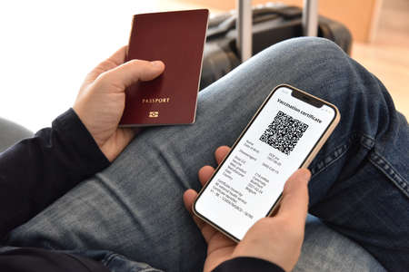 Man holding passport and mobile phone with digital certificate of vaccination against , a negative PCR test or recovery from . Travel concept during pandemic. Imagens