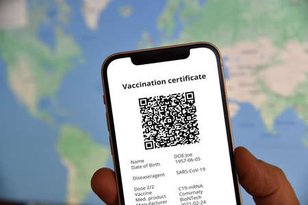 Mobile phone  with digital certificate of vaccination against  in front of the world map. Travel and tourism concept during pandemic.
