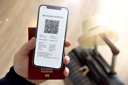 Vacation in the era of  A mans hand holds a mobile phone with a digital certificate against  and a passport, next to a travel bag.
