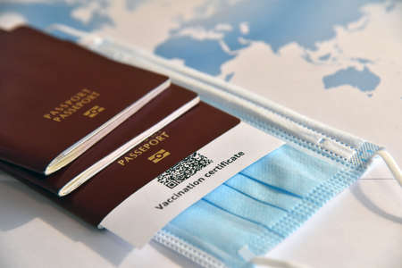 Travel in the era of . Passports, certificate of vaccination against  and face mask in front of the world map.