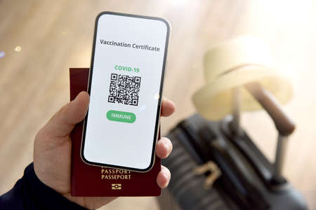 Travel and tourism concept during coronavirus pandemic. Man holding passport and mobile phone with digital certificate of vaccination against Covid-19, a negative PCR test or recovery from Covid-19.