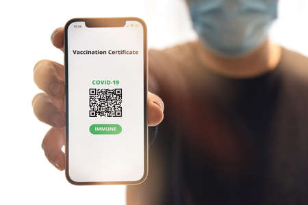 Digital certificate of vaccination against Covid-19. Man with face mask holding mobile phone with digital certificate of vaccination against Covid-19, a negative PCR test or recovery from coronavirus. Imagens