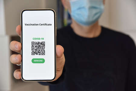 Digital certificate of vaccination against Covid-19. Man with face mask holding mobile phone with digital certificate of vaccination against Covid-19, a negative PCR test or recovery from coronavirus.