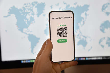 Travel and tourism concept during coronavirus pandemic. Smartphone with digital certificate of vaccination against Covid-19 in front of the world map.