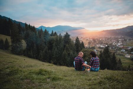 Romantic picnic of couple in love mountain view at sunset. Outdoor portrait of couple enjoying the campfire in the forest. travel, camping, couple, people, tent, fire, tourist Stock fotó