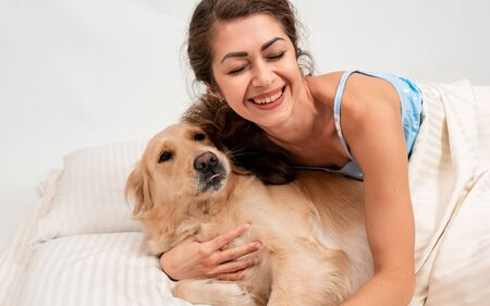 Female woman sleep in pajamas lying in bed embracing with her big golden retriever dog. Romantic relationship human and dog concept Archivio Fotografico